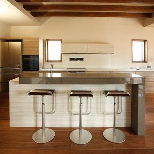 他の地域の大きいモダンスタイルのおしゃれなキッチン (アンダーカウンターシンク、インセット扉のキャビネット、ベージュのキャビネット、人工大理石カウンター、白いキッチンパネル、シルバーの調理設備の、無垢フローリング、茶色い床、白いキッチンカウンター) の写真
