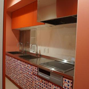 Geschlossene, Einzeilige Tropenstil Küche mit Unterbauwaschbecken, Kassettenfronten, roten Schränken, Edelstahl-Arbeitsplatte, Küchenrückwand in Weiß, Glasrückwand, Küchengeräten aus Edelstahl, Linoleum, Kücheninsel, beigem Boden, grauer Arbeitsplatte und Tapetendecke in Tokio