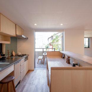 他の地域のアジアンスタイルのおしゃれなキッチン (一体型シンク、フラットパネル扉のキャビネット、淡色木目調キャビネット、ステンレスカウンター、緑のキッチンパネル、モザイクタイルのキッチンパネル、パネルと同色の調理設備、淡色無垢フローリング、ベージュの床、グレーのキッチンカウンター) の写真