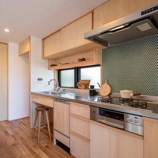 他の地域のアジアンスタイルのおしゃれなペニンシュラキッチン (一体型シンク、フラットパネル扉のキャビネット、淡色木目調キャビネット、ステンレスカウンター、無垢フローリング、茶色い床) の写真