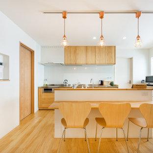 他の地域の中くらいのアジアンスタイルのおしゃれなキッチン (フラットパネル扉のキャビネット、白いキャビネット、木材カウンター、ガラス板のキッチンパネル、ベージュの床、茶色いキッチンカウンター) の写真
