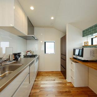 東京都下の中くらいの地中海スタイルのおしゃれなキッチン (一体型シンク、フラットパネル扉のキャビネット、白いキャビネット、ステンレスカウンター、白いキッチンパネル、セラミックタイルのキッチンパネル、無垢フローリング、茶色い床、茶色いキッチンカウンター) の写真