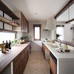 Idées déco pour une cuisine parallèle contemporaine avec un évier posé, un placard avec porte à panneau encastré, des portes de placard en bois sombre, un plan de travail en carrelage et un électroménager blanc.