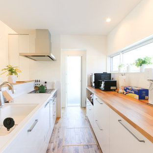 Small contemporary single-wall open plan kitchen in Other with an integrated sink, flat-panel cabinets, white cabinets, solid surface benchtops, white splashback, black appliances, medium hardwood floors, a peninsula, brown floor and brown benchtop.