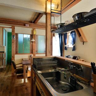 東京23区のシャビーシック調のおしゃれなキッチン (ステンレスカウンター、メタリックのキッチンパネル、サブウェイタイルのキッチンパネル、濃色無垢フローリング) の写真