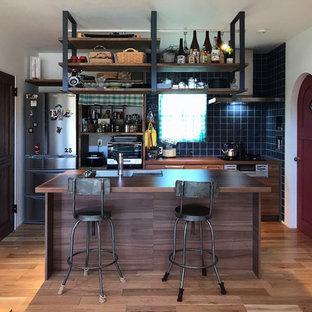 Foto di una cucina moderna con lavello integrato, ante lisce, ante marroni, top in laminato, paraspruzzi blu, paraspruzzi in gres porcellanato, elettrodomestici neri, parquet chiaro, isola, pavimento beige e top marrone