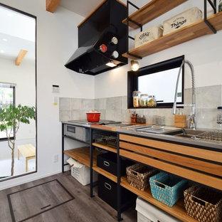 他の地域のインダストリアルスタイルのおしゃれなキッチン (シングルシンク、オープンシェルフ、ステンレスカウンター、グレーのキッチンパネル、グレーの床) の写真