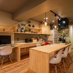 東京23区のアジアンスタイルのおしゃれなキッチン (シングルシンク、フラットパネル扉のキャビネット、淡色木目調キャビネット、ステンレスカウンター、無垢フローリング、茶色い床、茶色いキッチンカウンター) の写真