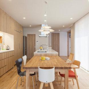 他の地域の中くらいのアジアンスタイルのおしゃれなキッチン (アンダーカウンターシンク、フラットパネル扉のキャビネット、中間色木目調キャビネット、パネルと同色の調理設備、無垢フローリング、ベージュの床、ベージュのキッチンカウンター) の写真