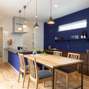他の地域の中くらいのアジアンスタイルのおしゃれなキッチン (フラットパネル扉のキャビネット、中間色木目調キャビネット、木材カウンター、パネルと同色の調理設備、淡色無垢フローリング、アイランドなし、ベージュの床、茶色いキッチンカウンター) の写真