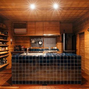 Foto de cocina de galera, asiática, abierta, con fregadero encastrado, armarios abiertos, puertas de armario de madera oscura, encimera de azulejos, suelo de madera en tonos medios, una isla, suelo marrón y encimeras azules