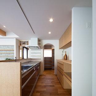 他の地域のコンテンポラリースタイルのおしゃれなペニンシュラキッチン (一体型シンク、フラットパネル扉のキャビネット、茶色いキャビネット、ステンレスカウンター、無垢フローリング、茶色い床、茶色いキッチンカウンター) の写真