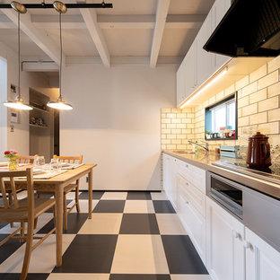 他の地域のインダストリアルスタイルのおしゃれなペニンシュラキッチン (一体型シンク、レイズドパネル扉のキャビネット、白いキャビネット、ステンレスカウンター、マルチカラーの床) の写真