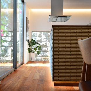 Пример оригинального дизайна интерьера: кухня в стиле модернизм с обеденным столом, бежевым фартуком, паркетным полом среднего тона, островом и розовым полом