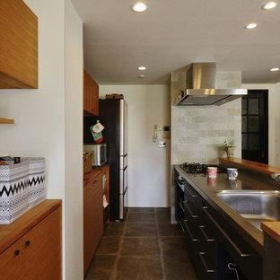コンテンポラリースタイルのおしゃれなキッチン (シングルシンク、フラットパネル扉のキャビネット、中間色木目調キャビネット、ステンレスカウンター、シルバーの調理設備、グレーの床、茶色いキッチンカウンター) の写真