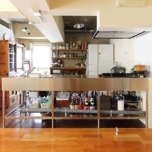 東京23区のインダストリアルスタイルのおしゃれなキッチン (シングルシンク、オープンシェルフ、ステンレスキャビネット、ステンレスカウンター、濃色無垢フローリング、茶色い床) の写真