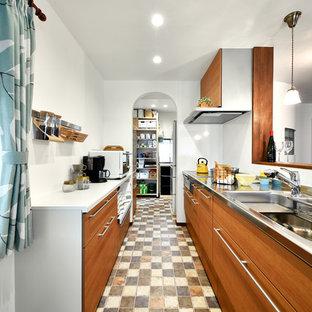 他の地域のコンテンポラリースタイルのおしゃれなキッチン (ダブルシンク、フラットパネル扉のキャビネット、茶色いキャビネット、ステンレスカウンター、マルチカラーの床) の写真