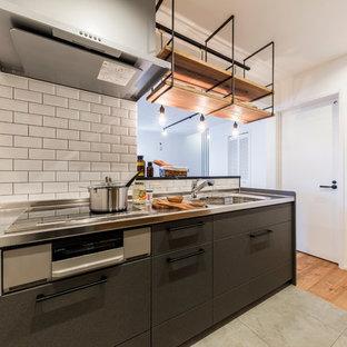 東京都下のインダストリアルスタイルのおしゃれなキッチン (シングルシンク、フラットパネル扉のキャビネット、黒いキャビネット、白いキッチンパネル、サブウェイタイルのキッチンパネル、コンクリートの床、グレーの床) の写真