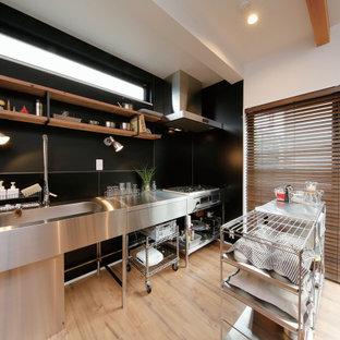 東京都下の中くらいのインダストリアルスタイルのおしゃれなキッチン (一体型シンク、オープンシェルフ、ステンレスキャビネット、ステンレスカウンター、黒いキッチンパネル、セラミックタイルのキッチンパネル、無垢フローリング、茶色い床、グレーのキッチンカウンター) の写真
