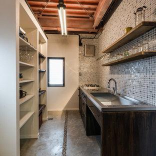 他の地域のインダストリアルスタイルのおしゃれなキッチン (シングルシンク、フラットパネル扉のキャビネット、濃色木目調キャビネット、ステンレスカウンター、マルチカラーのキッチンパネル、コンクリートの床) の写真