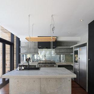 他の地域のインダストリアルスタイルのおしゃれなキッチン (コンクリートカウンター、シルバーの調理設備の、濃色無垢フローリング、ドロップインシンク、茶色い床) の写真