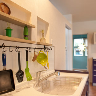 This is an example of a single-wall open plan kitchen in Other with an integrated sink, purple cabinets, composite countertops, stainless steel appliances, plywood flooring, an island and brown floors.