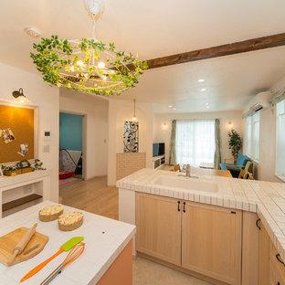 他の地域の地中海スタイルのおしゃれなキッチン (ドロップインシンク、落し込みパネル扉のキャビネット、淡色木目調キャビネット、タイルカウンター、淡色無垢フローリング) の写真