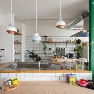東京23区のコンテンポラリースタイルのおしゃれなコの字型キッチン (一体型シンク、オープンシェルフ、ステンレスカウンター、白いキッチンパネル、サブウェイタイルのキッチンパネル、シルバーの調理設備) の写真