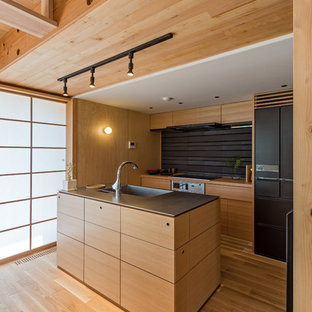 Asian galley open plan kitchen in Other with an integrated sink, flat-panel cabinets, medium wood cabinets, brown splashback, black appliances, medium hardwood floors and with island.