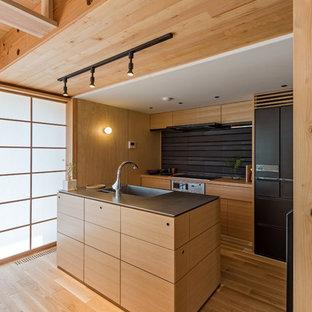 他の地域のアジアンスタイルのおしゃれなキッチン (一体型シンク、フラットパネル扉のキャビネット、中間色木目調キャビネット、茶色いキッチンパネル、黒い調理設備、無垢フローリング) の写真
