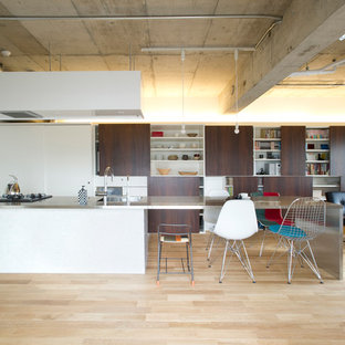 Design ideas for an industrial single-wall open plan kitchen in Tokyo with a peninsula, stainless steel benchtops, light hardwood floors, an integrated sink, dark wood cabinets, metallic splashback, black appliances, beige floor and white benchtop.