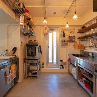 東京23区のトラディショナルスタイルのおしゃれなキッチン (シルバーの調理設備の、シングルシンク、フラットパネル扉のキャビネット、ターコイズのキャビネット、ステンレスカウンター、コンクリートの床、グレーの床) の写真