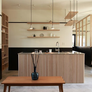 他の地域のアジアンスタイルのおしゃれなアイランドキッチン (シングルシンク、ステンレスカウンター、コンクリートの床、グレーの床) の写真
