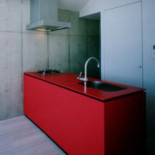 Diseño de cocina lineal, minimalista, pequeña, abierta, con fregadero bajoencimera, puertas de armario rojas, encimera de acrílico, electrodomésticos de acero inoxidable, suelo de contrachapado, suelo beige y encimeras rojas