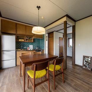 他の地域の小さいアジアンスタイルのおしゃれなキッチン (ステンレスカウンター、緑のキッチンパネル、茶色い床、アンダーカウンターシンク、インセット扉のキャビネット、茶色いキャビネット、セラミックタイルのキッチンパネル、シルバーの調理設備の、濃色無垢フローリング、アイランドなし、茶色いキッチンカウンター) の写真