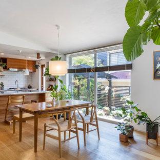 他の地域の中サイズのアジアンスタイルのおしゃれなキッチン (アンダーカウンターシンク、フラットパネル扉のキャビネット、中間色木目調キャビネット、白いキッチンパネル、サブウェイタイルのキッチンパネル、無垢フローリング、ベージュの床、グレーのキッチンカウンター) の写真