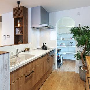 他の地域の小さい北欧スタイルのおしゃれなキッチン (一体型シンク、レイズドパネル扉のキャビネット、中間色木目調キャビネット、人工大理石カウンター、白いキッチンパネル、磁器タイルのキッチンパネル、黒い調理設備、無垢フローリング、アイランドなし、マルチカラーの床、茶色いキッチンカウンター) の写真