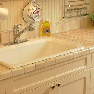 Modelo de cocina lineal, tradicional, pequeña, sin isla, con fregadero encastrado, armarios con paneles empotrados, puertas de armario blancas, encimera de azulejos y encimeras rosas