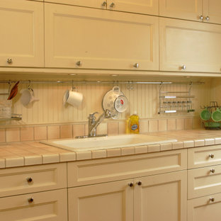 This is an example of a small traditional single-wall kitchen in Osaka with a drop-in sink, recessed-panel cabinets, white cabinets, tile benchtops, no island and pink benchtop.
