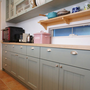 Design ideas for a mid-sized traditional galley kitchen in Osaka with an undermount sink, recessed-panel cabinets, green cabinets, solid surface benchtops, panelled appliances, no island and orange benchtop.