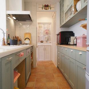 Foto de cocina de galera, tradicional, de tamaño medio, sin isla, con fregadero bajoencimera, armarios con paneles empotrados, puertas de armario verdes, encimera de acrílico, electrodomésticos con paneles y encimeras naranjas