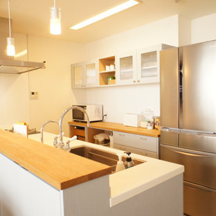 Foto di una cucina classica di medie dimensioni con lavello sottopiano, ante in stile shaker, ante turchesi, top in legno, elettrodomestici bianchi, nessuna isola e top bianco
