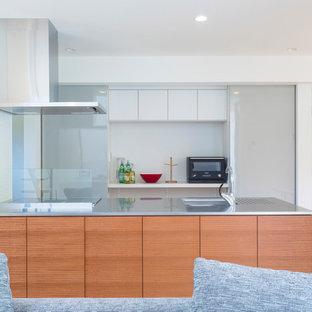 他の地域のモダンスタイルのおしゃれなキッチン (シングルシンク、フラットパネル扉のキャビネット、中間色木目調キャビネット、ステンレスカウンター、ガラスまたは窓のキッチンパネル、淡色無垢フローリング、茶色い床) の写真