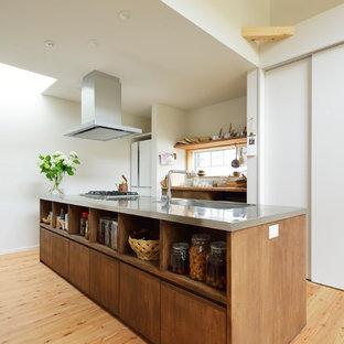 他の地域の小さいモダンスタイルのおしゃれなキッチン (一体型シンク、茶色いキャビネット、ステンレスカウンター、シルバーの調理設備の、無垢フローリング、ベージュの床、フラットパネル扉のキャビネット) の写真