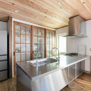 他の地域のインダストリアルスタイルのおしゃれなキッチン (ステンレスカウンター、無垢フローリング、シングルシンク) の写真