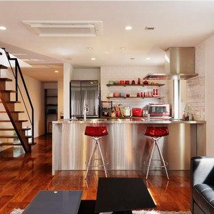 コンテンポラリースタイルのおしゃれなキッチン (ステンレスカウンター、メタリックのキッチンパネル、シングルシンク、塗装フローリング、茶色い床) の写真