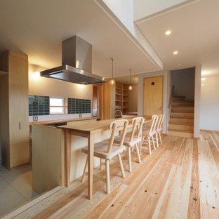 東京都下の広いアジアンスタイルのおしゃれなキッチン (フラットパネル扉のキャビネット、淡色木目調キャビネット、木材カウンター、パネルと同色の調理設備、淡色無垢フローリング、ベージュの床、ベージュのキッチンカウンター、緑のキッチンパネル、サブウェイタイルのキッチンパネル) の写真