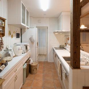 他の地域のカントリー風おしゃれなキッチン (人工大理石カウンター、白いキッチンパネル、白い調理設備、テラコッタタイルの床、オレンジの床、白いキッチンカウンター、シングルシンク、落し込みパネル扉のキャビネット) の写真