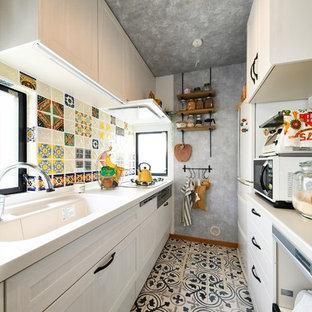 他の地域の地中海スタイルのおしゃれなキッチン (一体型シンク、落し込みパネル扉のキャビネット、白いキャビネット、マルチカラーの床) の写真