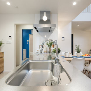 Nautical single-wall open plan kitchen in Other with a single-bowl sink, beaded cabinets, medium wood cabinets, stainless steel worktops, white splashback, black appliances, plywood flooring, beige floors and beige worktops.